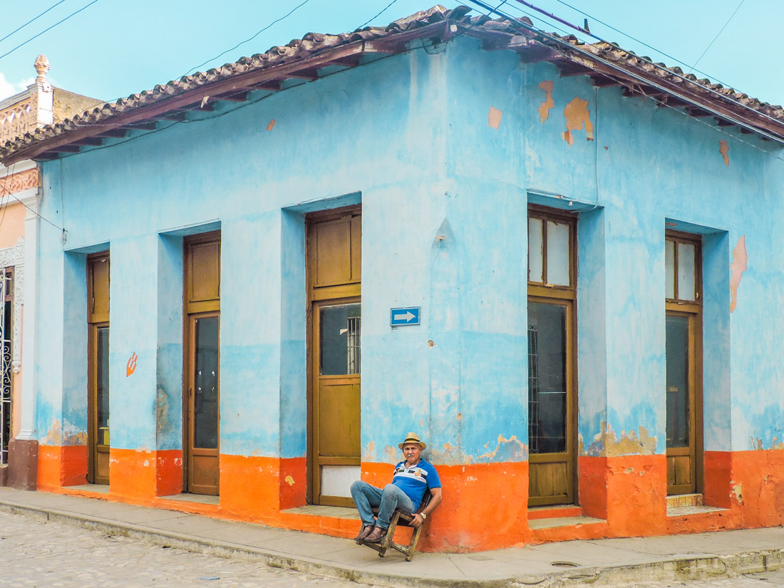 Man sitting outside a blue building in Trinidad, Cuba