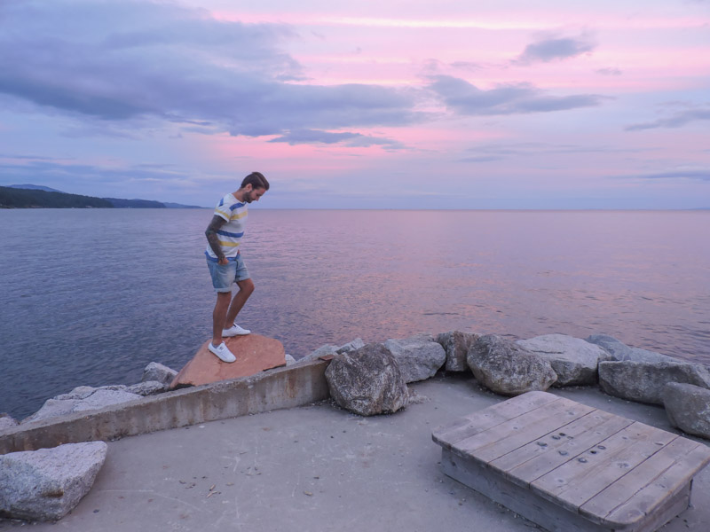 Man standing on large stone, ocean in background with pink sunset at Robert Creek Beach Pier_