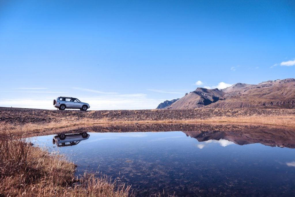Car Iceland landscape, reflection in water