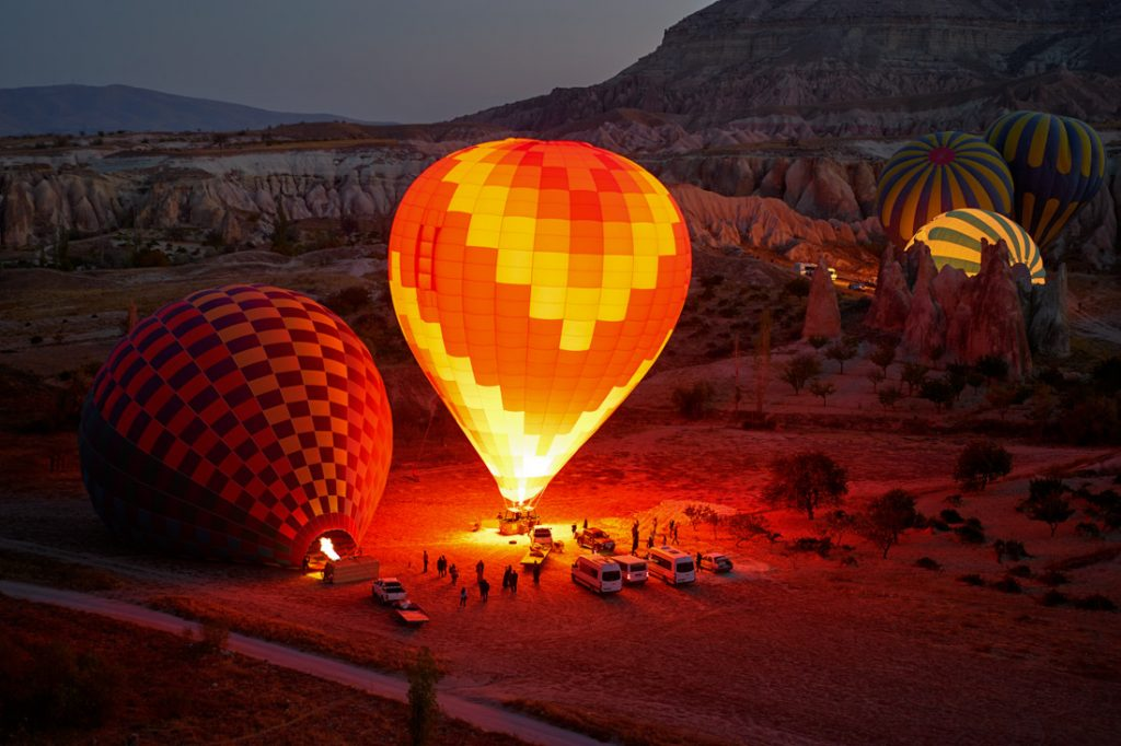Hot air balloons lighting up Cappadocia Turkey sunrise