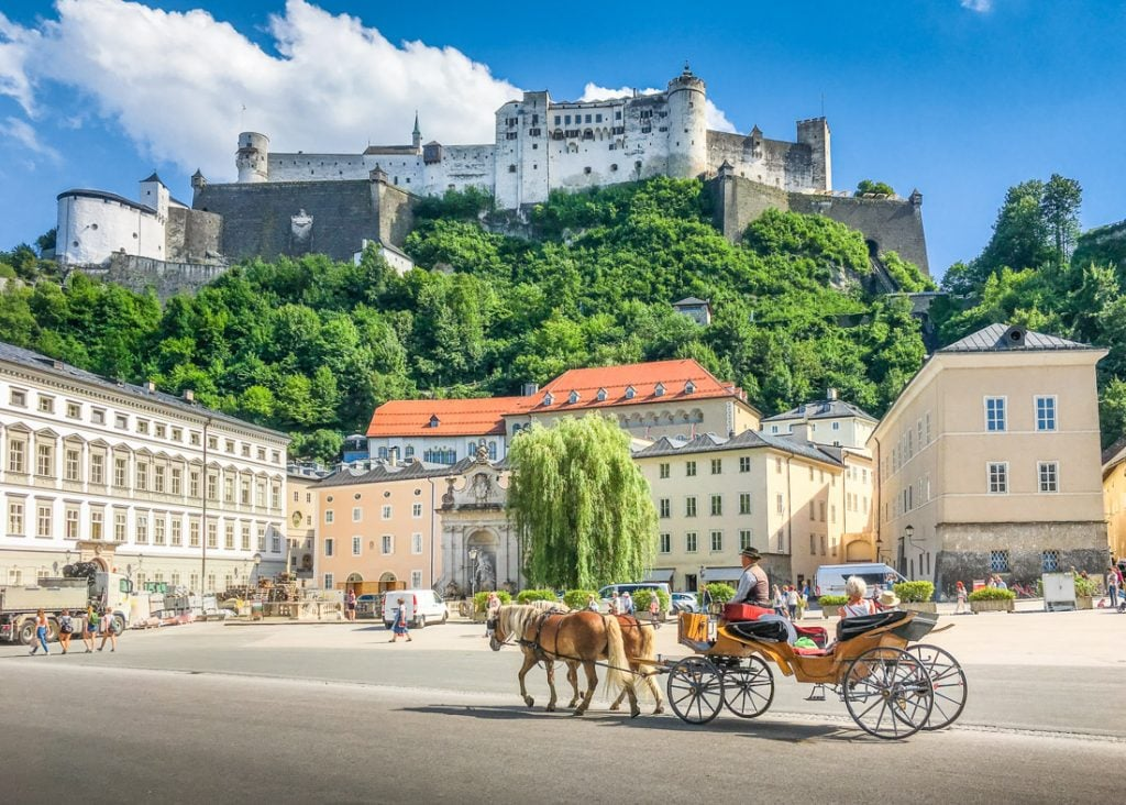 Salzburg with traditonal horse-drawn Fiaker carriage and famous Hohensalzburg Fortress