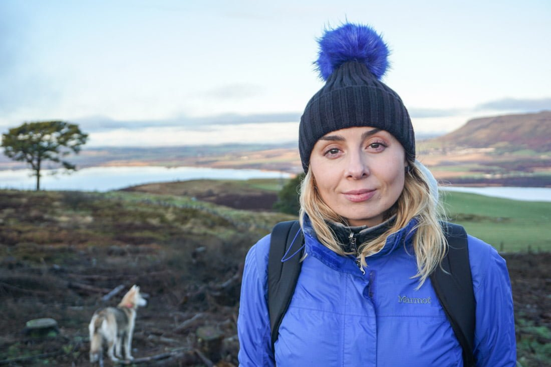 Benarty Hill hike, Fife Scotland. Gemma wearing blue Marmot Precip jacket, bag, hat. Bowie the dog in background. Trees, loch._