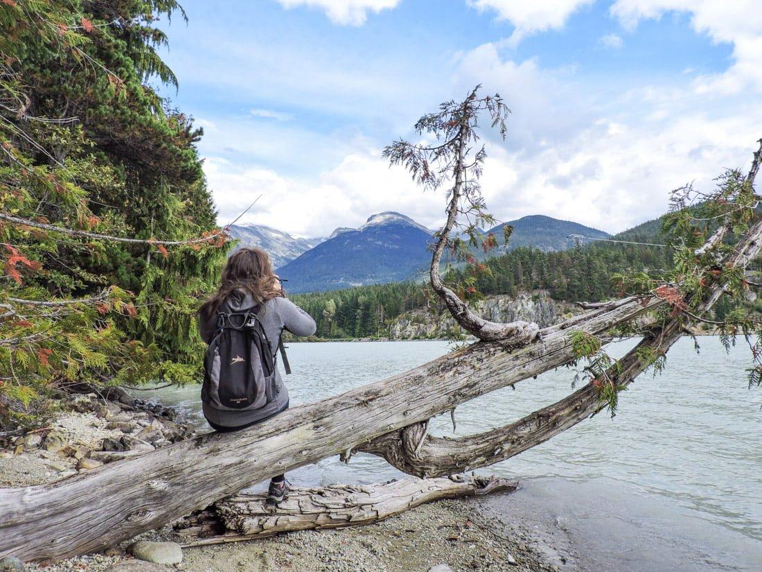 Whistler hikes, Canada. Gemma taking photo of mountain sitting on tree. Lake water._