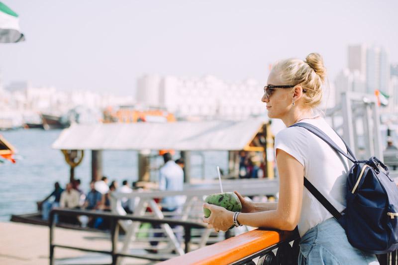 Dubai travel tips -Blonde women wearing sunglasses posing near a Dubai boat